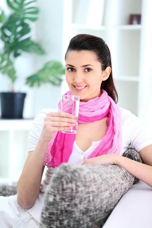 Frau hält ein Glas mit Wasser an lizenzfreies stockfoto