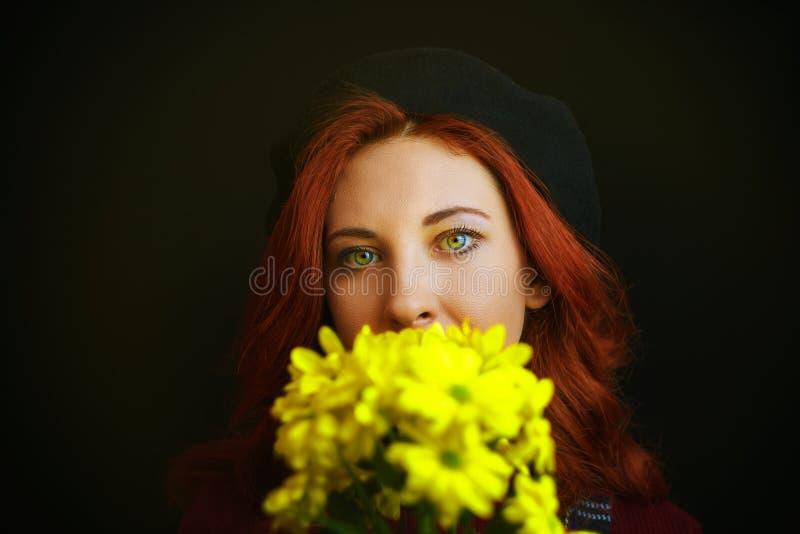 Frau hält eine gelbe Chrysantheme lizenzfreie stockfotografie