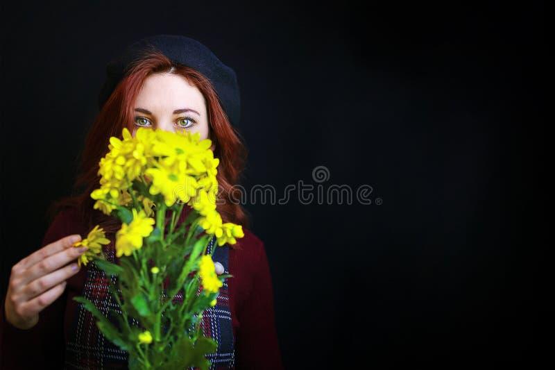 Frau hält eine gelbe Chrysantheme stockfoto