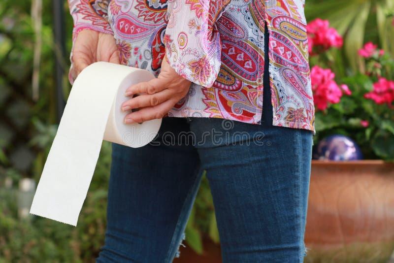Frau hält eine Toilettenrolle lizenzfreie stockfotografie