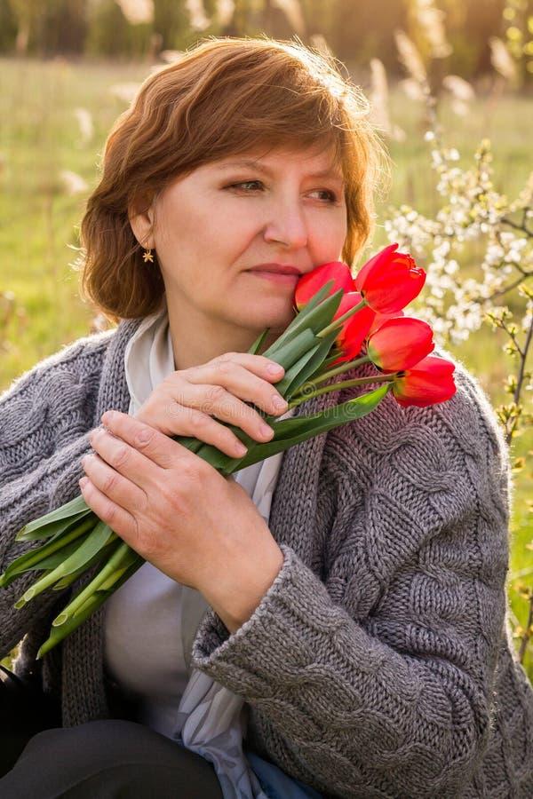 Frau hält einen Blumenstrauß der Tulpen an stockfotos