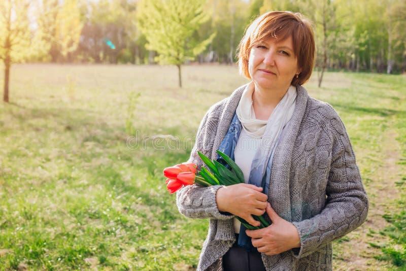 Frau hält einen Blumenstrauß der Tulpen an Sohn gibt der Mama eine Blume lizenzfreies stockfoto