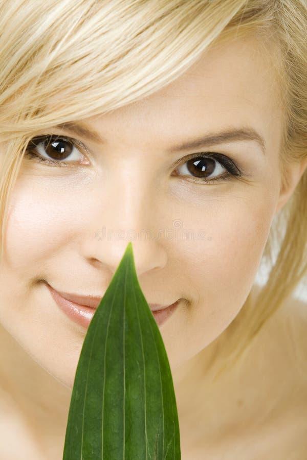 Frau hält frisches grünes Blatt an ihrem Gesicht lizenzfreie stockfotos