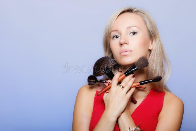 Frau hält Make-upbürsten nahe Gesicht. lizenzfreie stockbilder