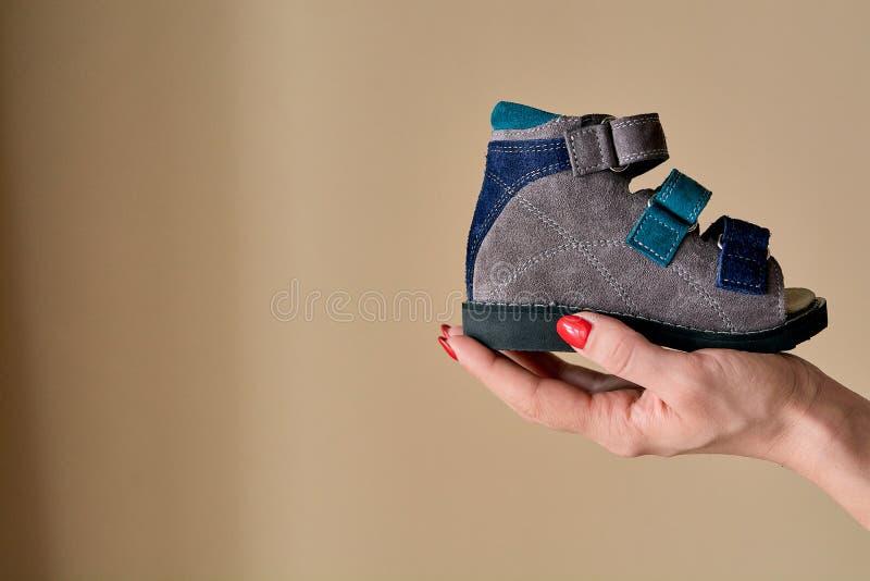 Frau hält Nahaufnahme Sandalen des orthopädischen Schuhes speziellen Kinder gemacht vom echten Leder stockfotografie