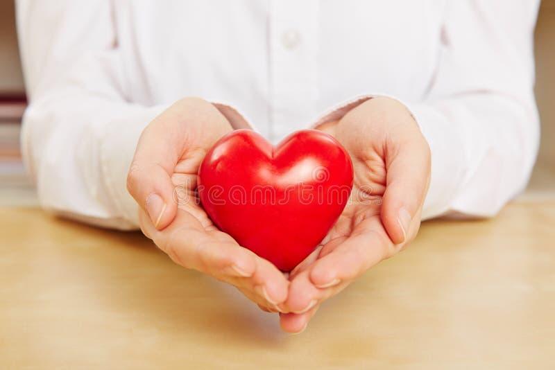 Frau hält rotes Herz in der Hand lizenzfreie stockfotografie