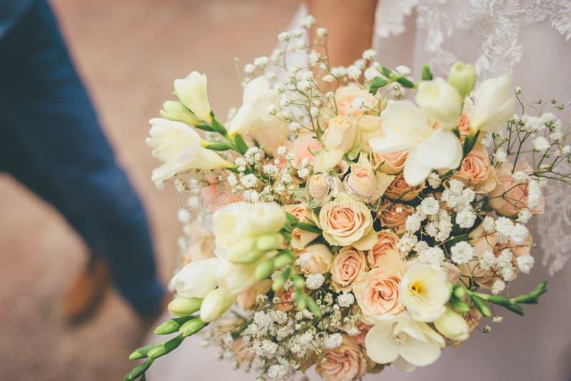 Frau hält schönen Hochzeitsblumenstrauß mit zwei Ringen in ihren Händen stockfotos