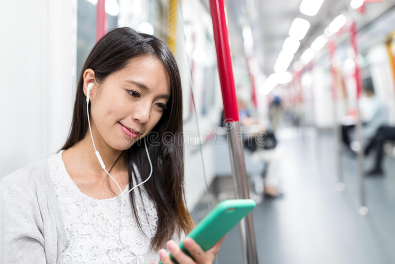 Frau hören auf Mobiltelefon mit Handfreiem Innerezug stockfoto