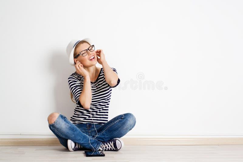 Frau an hörender Musik der Wand lizenzfreies stockbild