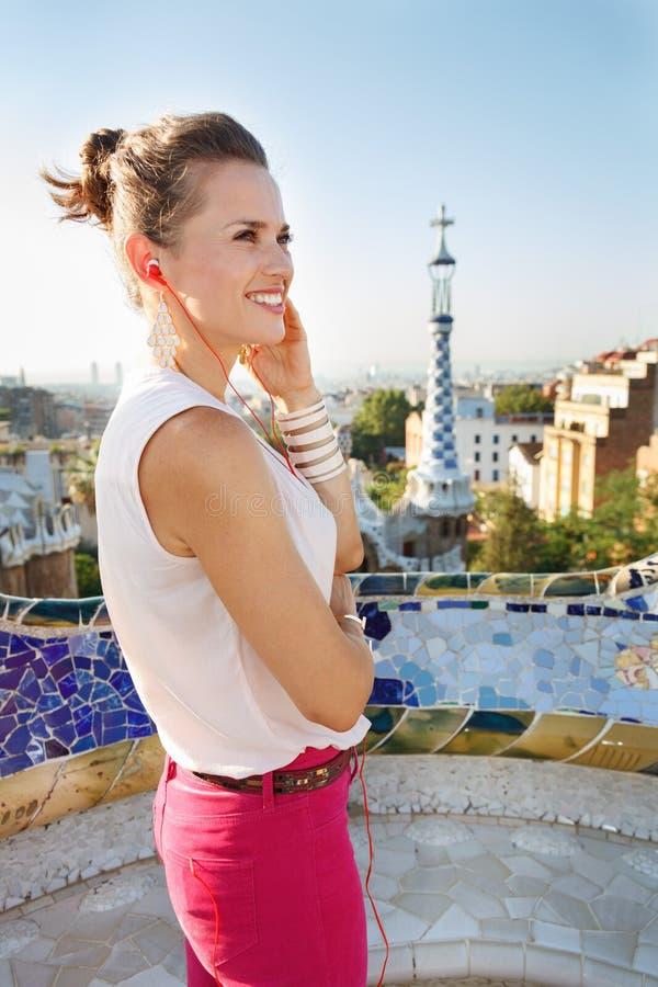 Frau hörendes audioguide im Park Guell, Barcelona, Spanien stockfoto