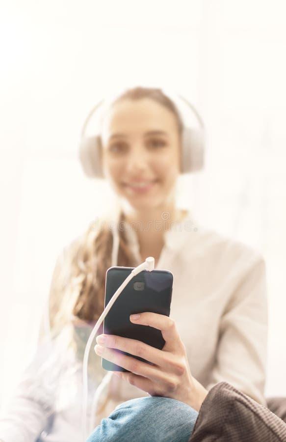 Frau hört zu Hause Musik stockbild
