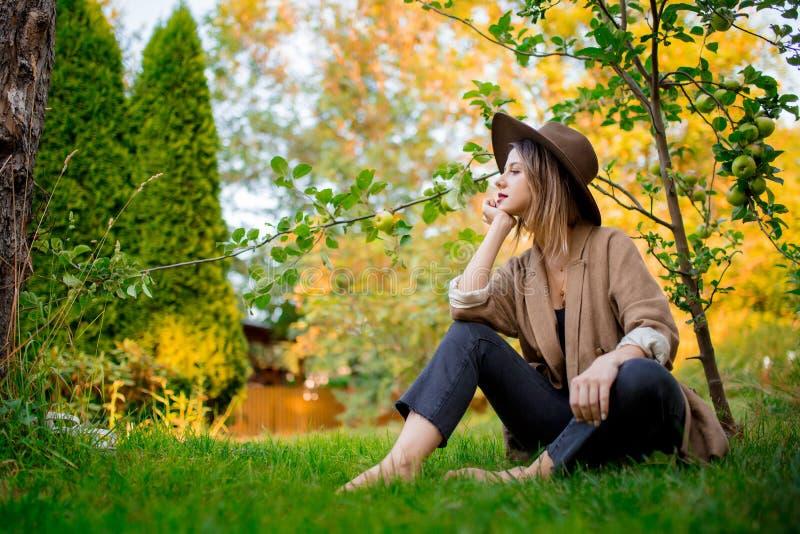Frau haben, in einem Garten nahe jungem Apfelbaum sich zu entspannen stockfotografie