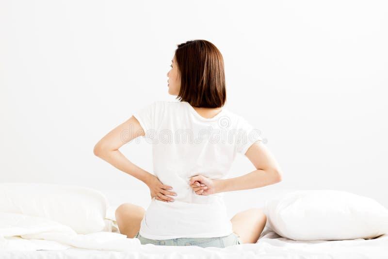 Frau haben Rückenschmerzen auf weißem Bett stockbilder