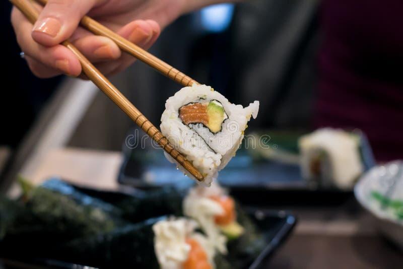 Frau hebt Uramaki-Sushirolle mit frischen Lachsen, Avocado und Philadelphia-Käse auf, bedeckt mit Samen des indischen Sesams lizenzfreies stockfoto