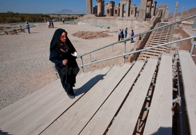 Frau in hijab traditionellem schwarzem Kleid gehend auf das Persepolis lizenzfreie stockfotos