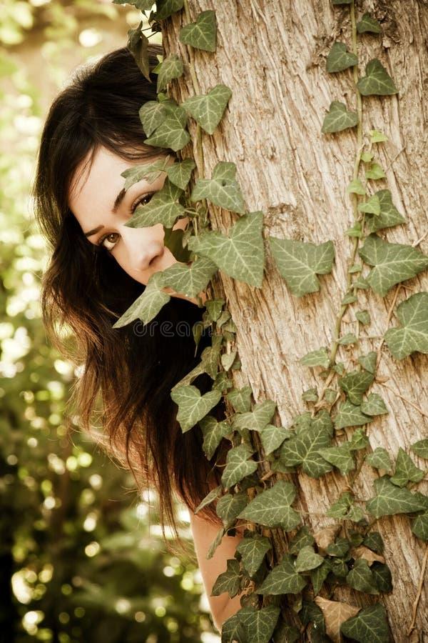 Frau hinter Blättern lizenzfreie stockfotografie