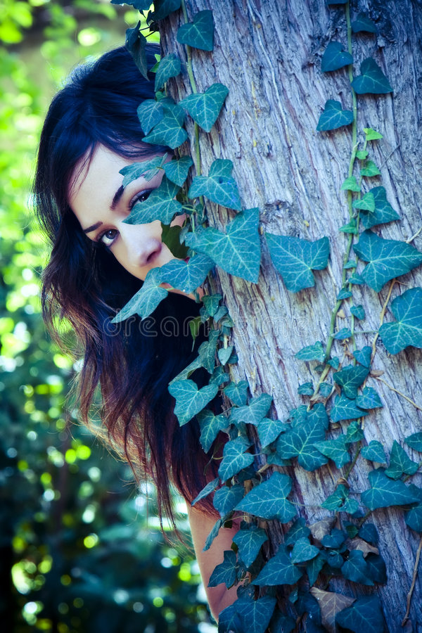 Frau hinter Blättern stockbild