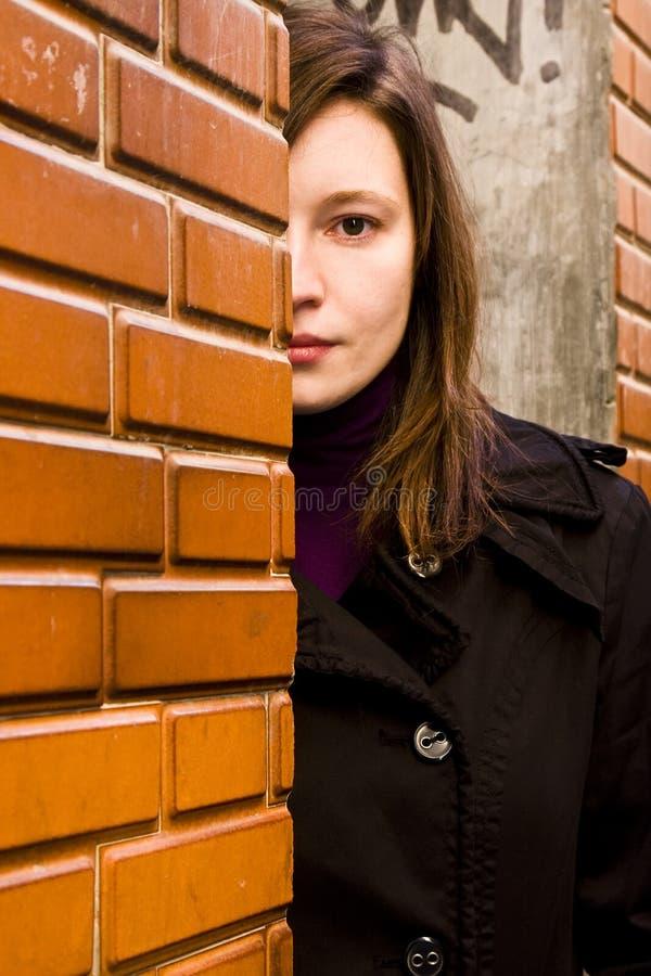 Frau hinter brickwall lizenzfreies stockbild