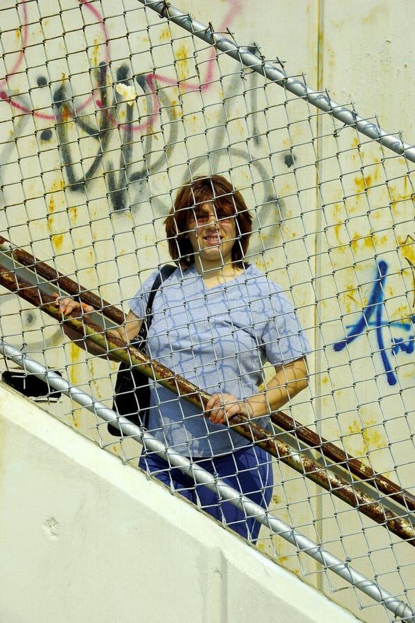 Frau hinter einem Zaun lizenzfreies stockfoto