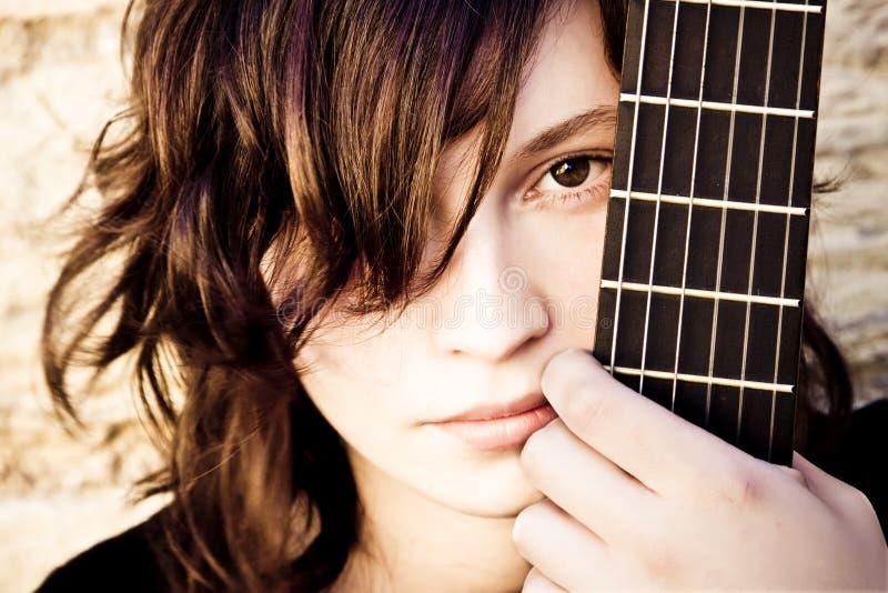 Frau hinter Gitarre fretboard lizenzfreies stockfoto