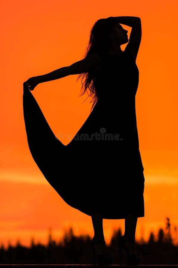 Frau am Hintergrund des Sonnenuntergangs lizenzfreies stockbild