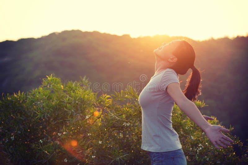 Frau hob Arme zum Sonnenaufgang auf die Gebirgsoberseite im Moring an stockfotografie