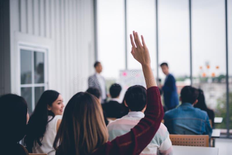 Frau hob oben Hände und Arme im SeminarKlassenzimmer, mit Sprecher am Konferenzseminar-Konferenzzimmer übereinzustimmen an stockfoto