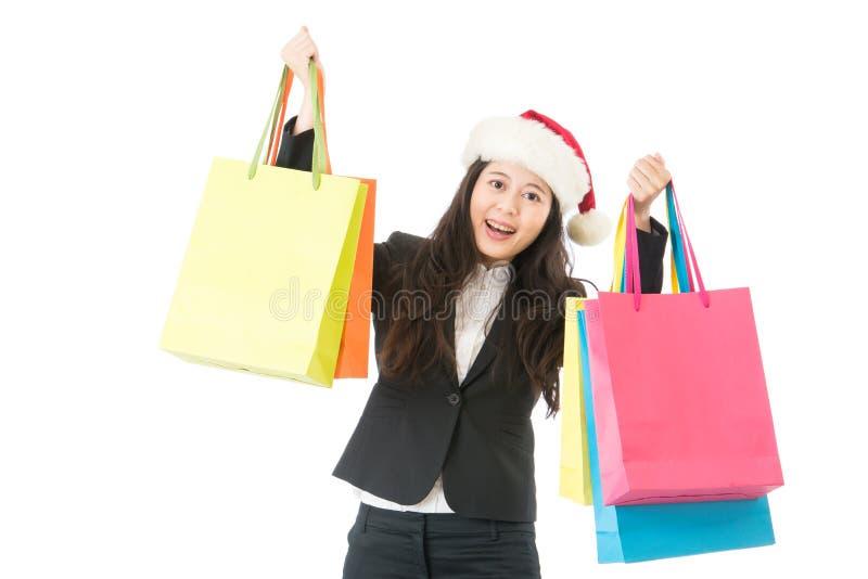 Frau Holding-Einkaufenbeuteln des Sankt-Hutes in den stehenden erregte getrennt auf weißem Hintergrund Geschäftsfrau im Sankt-Hut lizenzfreie stockfotos