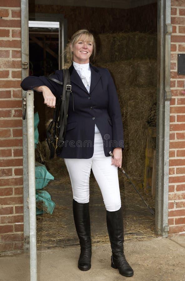 Frau hors Reiter, der an einer stabilen Tür steht stockfotografie