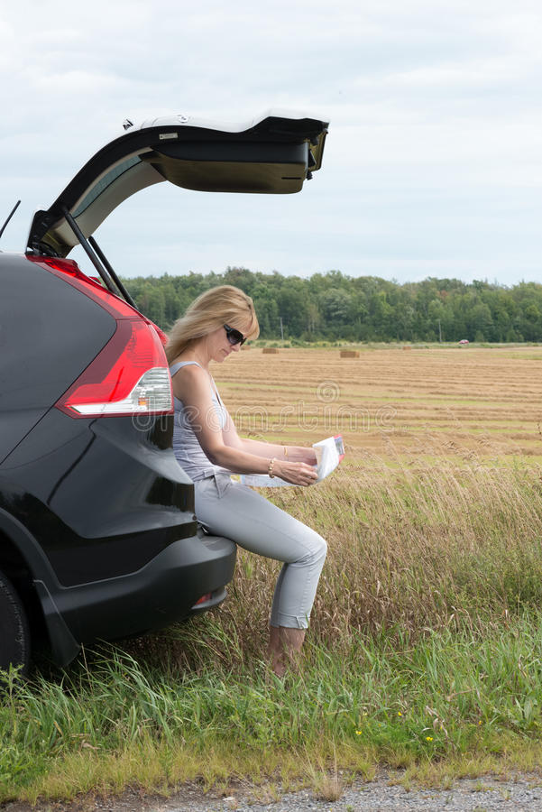 Frau im Auto, das Karte betrachtet stockbild