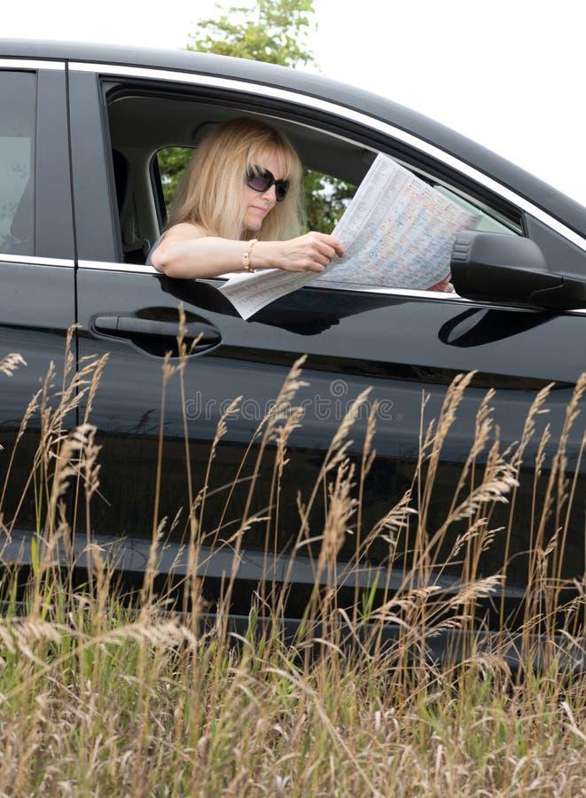 Frau im Auto, das Karte betrachtet lizenzfreie stockfotos