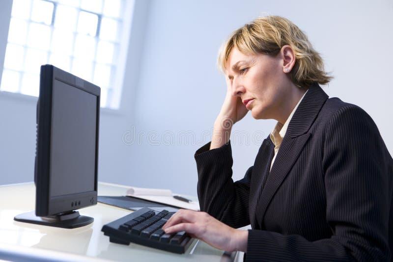 Frau im Büro auf Computer stockbild