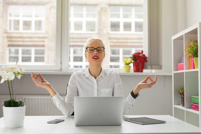 Frau im Büro meditierend stockbilder