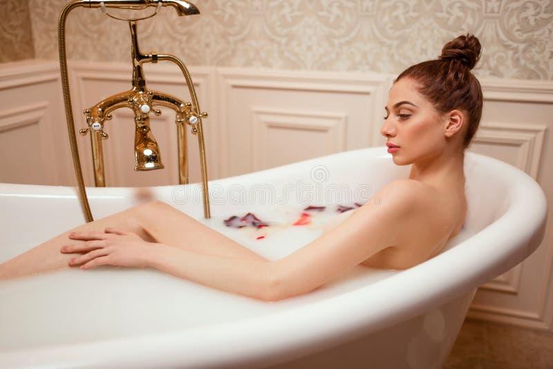 Frau im Bad mit den rosafarbenen Blumenblättern und Schaum lizenzfreie stockbilder