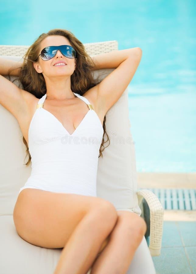 Frau im Badeanzug, der auf Liege Poolside legt stockfotografie