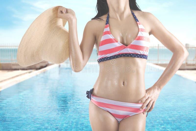 Frau im Badeanzug hält Hut am Pool stockbild