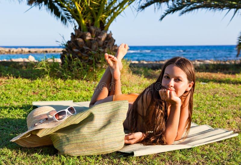 Frau im Badeanzug liegt auf grünem Gras lizenzfreie stockbilder