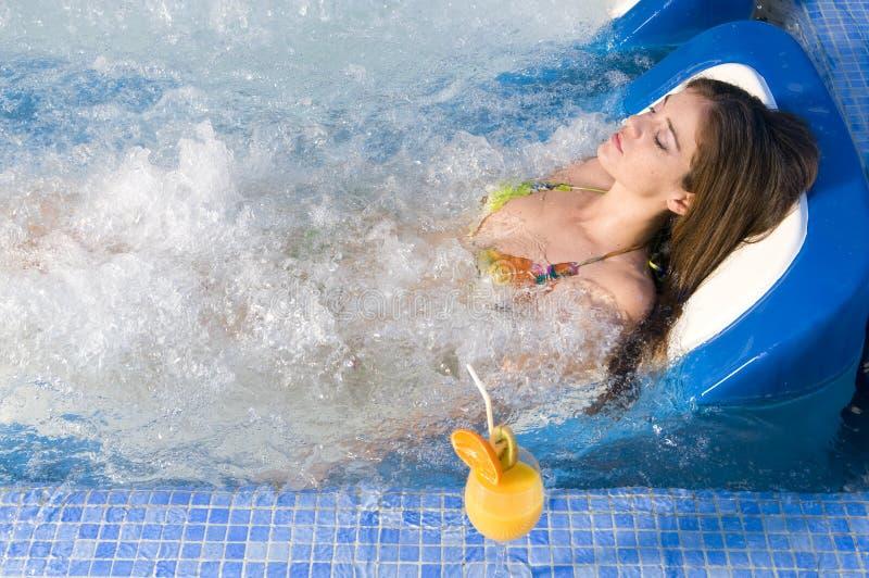 Frau im Badekurortbett, das einen Orangensaft isst stockbilder