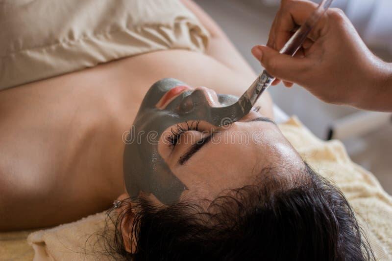 Frau im Badekurortsalon, der Gesichtsmaske durch Kosmetiker erhält stockfotografie