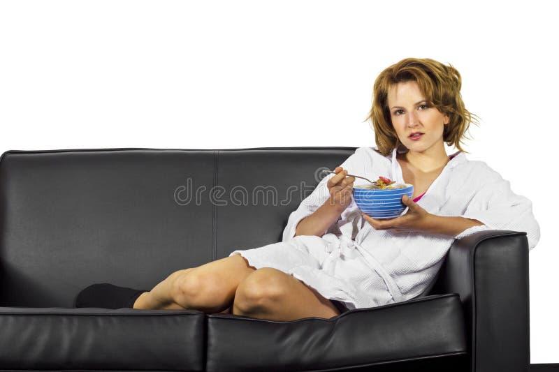 Frau im Bademantel Getreide essend stockfotos