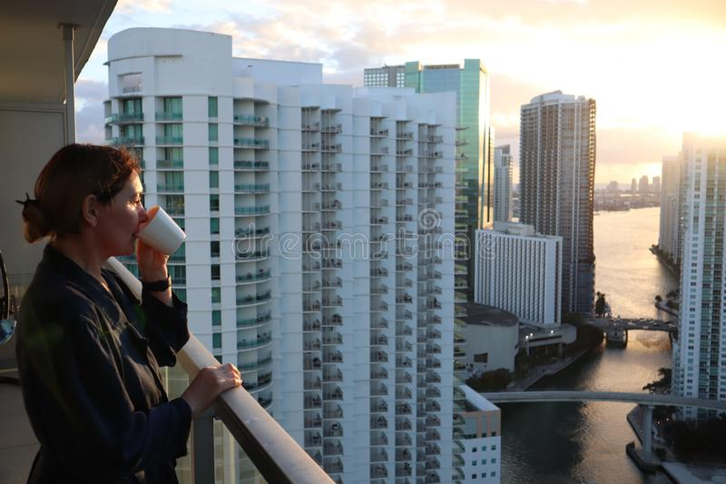 Frau im Bademantel ihren Morgenkaffee oder -tee auf einem im Stadtzentrum gelegenen Balkon trinkend Schöner Sonnenaufgang in im S stockfotos