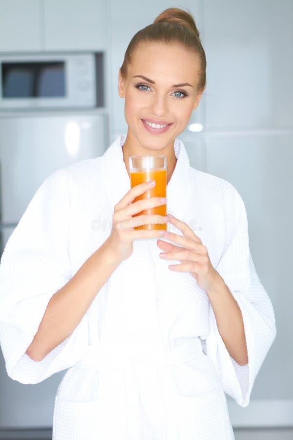 Frau im Bademantel Orangensaft trinkend lizenzfreies stockbild