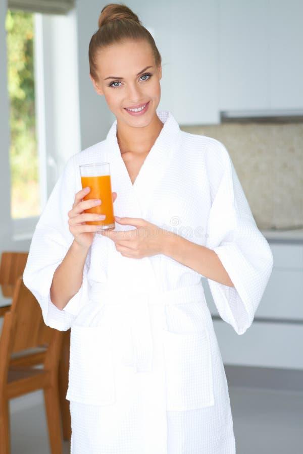 Frau im Bademantel Orangensaft trinkend lizenzfreie stockfotografie