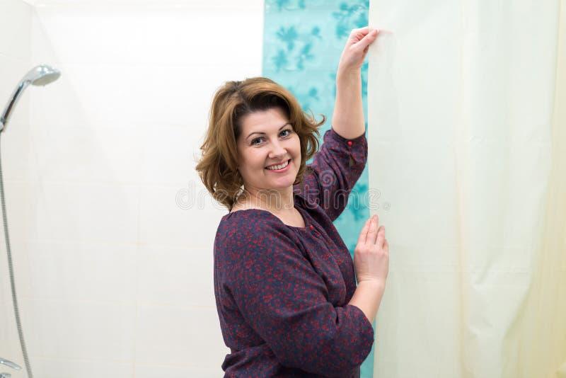 Frau im Badezimmer kümmert sich um Vorhang lizenzfreie stockfotografie