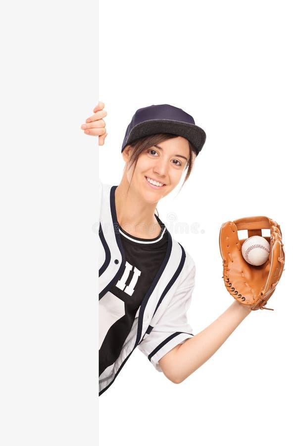Frau im Baseballtrikot, das hinter einer Platte aufwirft lizenzfreie stockfotografie