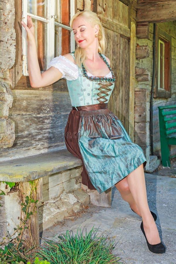 Frau im bayerischen Dirndl, träumend und sitzen auf einer Bank lizenzfreie stockfotos