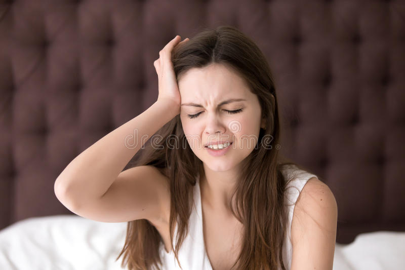 Frau im Bett, das unter Kopfschmerzen am Morgen leidet lizenzfreies stockfoto