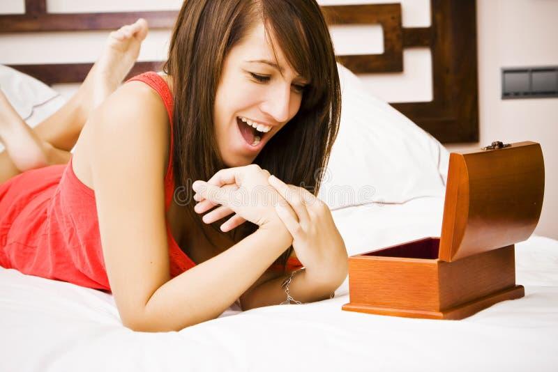 Frau im Bett ein Geschenk genießend lizenzfreie stockbilder