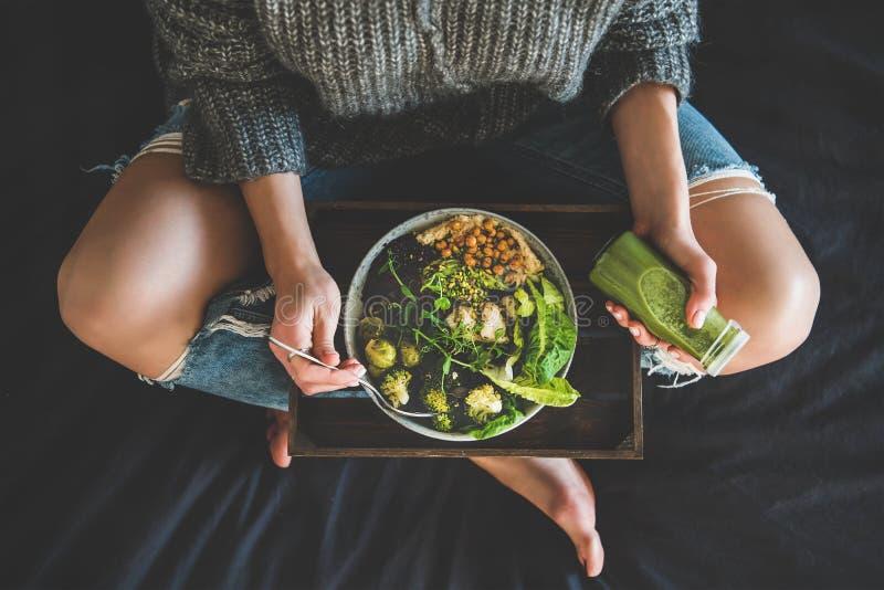 Frau im Bett Teller des strengen Vegetariers essend und Smoothie trinkend stockfotos