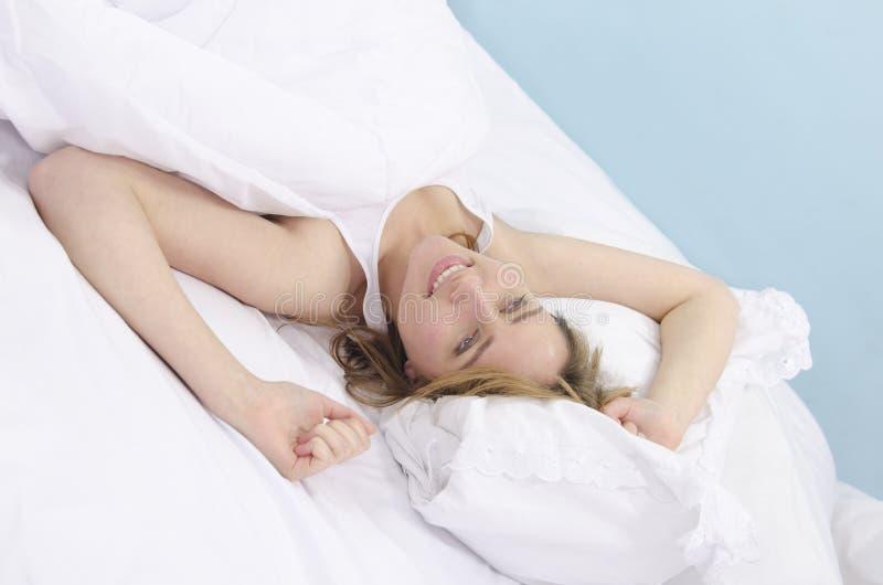 Frau im Bett träumend stockbild